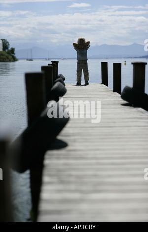 Boy on Jetty, Roseninsel Possenhofen, de l'île, le Lac de Starnberg, en Bavière, Allemagne Banque D'Images