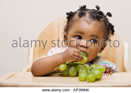Baby Girl eating grapes Banque D'Images
