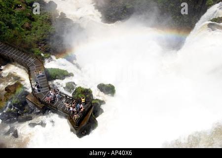 Brésil, chutes d'Iguaçu, imbibé de pulvérisation touristes sur un affût Banque D'Images