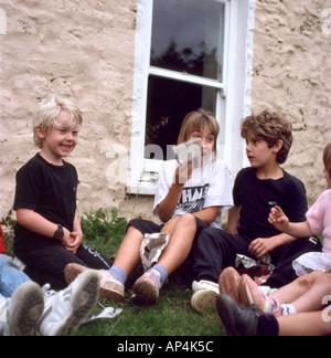 Des enfants assis à l'extérieur dans le jardin en jouant une note de la parcelle à un jeu d'anniversaire dans les Banque D'Images