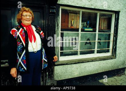 Femme en tricot aux couleurs vives et l'écharpe rouge l'extérieur d'un bar à Hay-on-Wye UK Banque D'Images