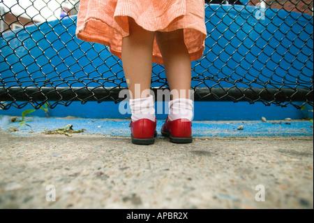 Jolie jambes de jeune fille avec des chaussures rouge et bleu robe à côté de clôture. Low angle bobby chaussettes Banque D'Images