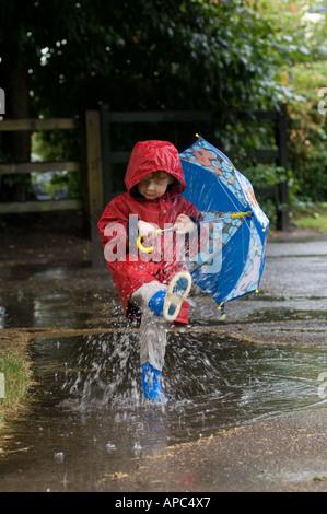 Petit garçon en manteau rouge et bleu s'éclabousser dans la pluie Banque D'Images