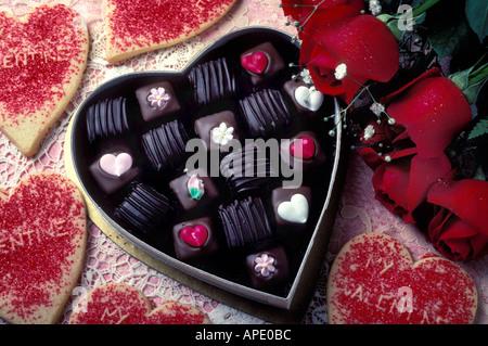 Bonbons en forme de coeur valentine en boîte avec les cookies et roses rouges Banque D'Images