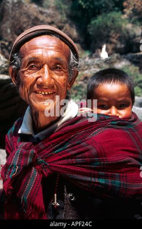Homme portant son petit-fils au Népal Banque D'Images