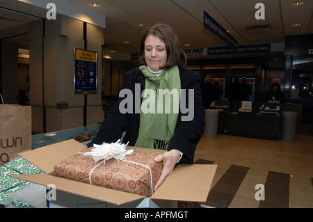 Femme mails son colis de Noël au Grand Central Post Office in NYC Banque D'Images