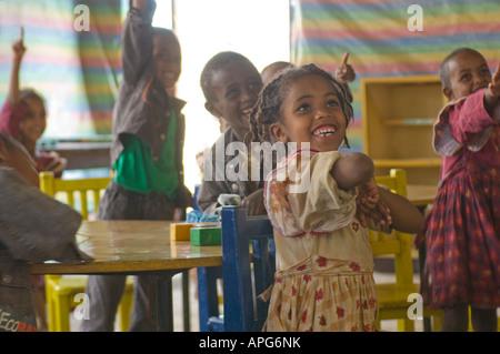 Les enfants sourire et a levé la main avec impatience de répondre à une question dans la salle de classe d'une école Banque D'Images