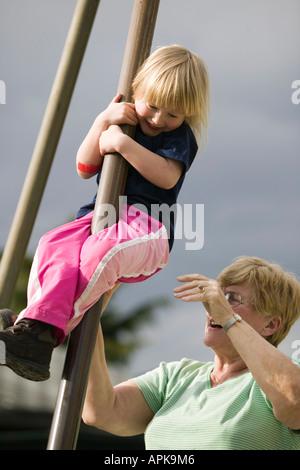 4 ans, fille, glissant sur un poste à une aire de jeux avec grand-mère Banque D'Images