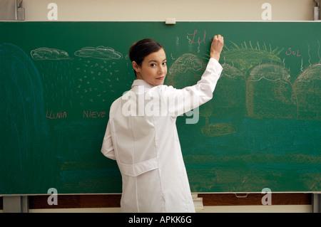 Dans une salle de classe de l'enseignant écrit sur tableau noir Banque D'Images