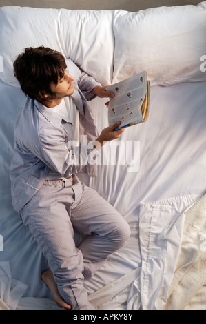 Man reading in bed Banque D'Images