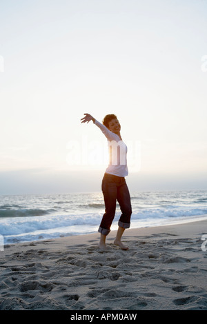 Mid adult woman running on beach Banque D'Images