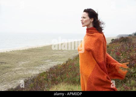 Jeune femme enveloppée de couverture sur beach Banque D'Images
