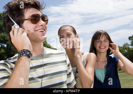 Les adolescents à écouter de la musique dans un parc Banque D'Images