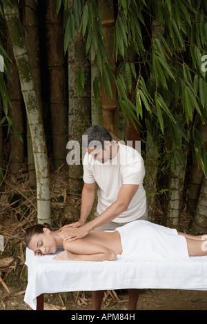 Massage homme jeune femme près d'arbres Banque D'Images