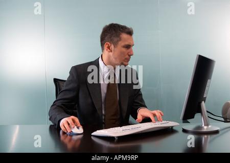 L'homme d'affaires à la recherche à l'écran de l'ordinateur Banque D'Images