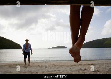 Mid adult man standing on beach, les jambes de la femme en premier plan, St John, US Virgin Islands, USA Banque D'Images