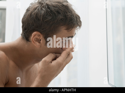 Mid adult man mettant en lentilles de contact Banque D'Images