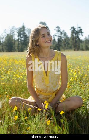 Jeune femme assise dans un champ de fleurs sauvages