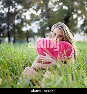 Teenage Girl Holding coussin en forme de coeur Banque D'Images