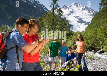 Mère et père review photo numérique de l'appareil photo sur des enfants en arrière-plan tout en randonnée sur glacier Banque D'Images