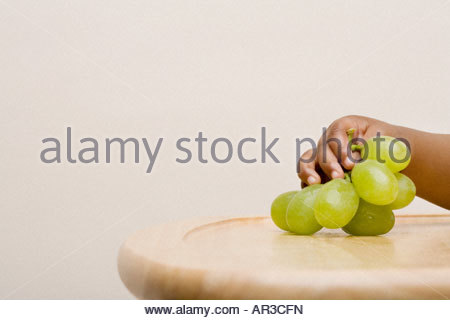 Baby holding grapes Banque D'Images