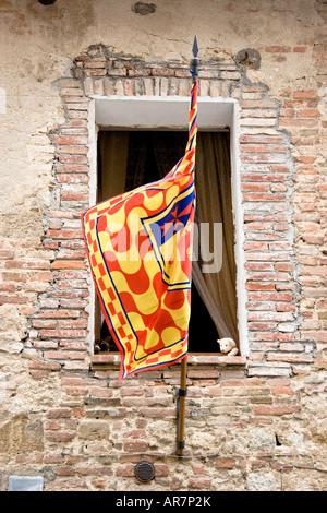 Un ours en peluche a l'air de pics à partir d'une chambre à coucher de l'enfant derrière un drapeau contrade à Montepulciano Banque D'Images