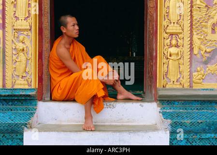 Un moine assis dans l'embrasure, temple Wat Xieng Thong, Luang Prabang, Laos Banque D'Images