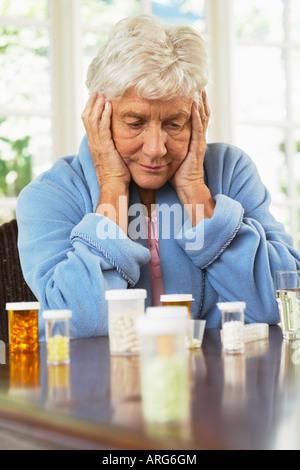 Senior Woman Looking at bouteilles de pilules Banque D'Images