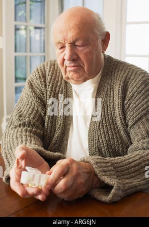 Man Looking at Pill Organizer Banque D'Images