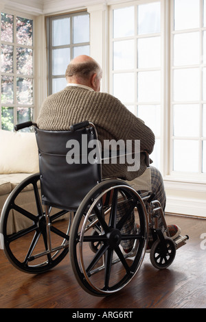 Senior Man in Wheelchair, Looking Out Window Banque D'Images
