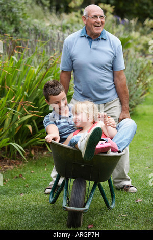 Grand-père poussant des petits-enfants dans la brouette