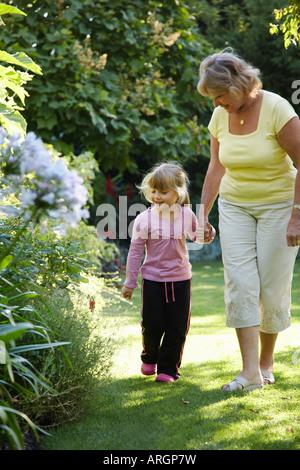 Grand-mère et petite-fille de marcher dans le jardin Banque D'Images