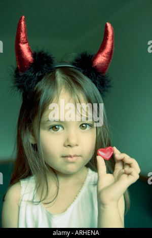 e6e07ac3c41c79 ... Jolie petite fille avec des cornes de diable tient dans la main douce  en forme de