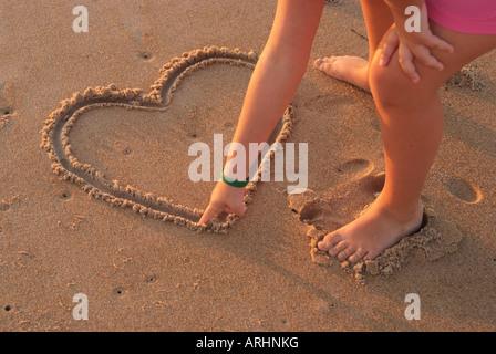 Girl attire l'coeur dans le sable Banque D'Images