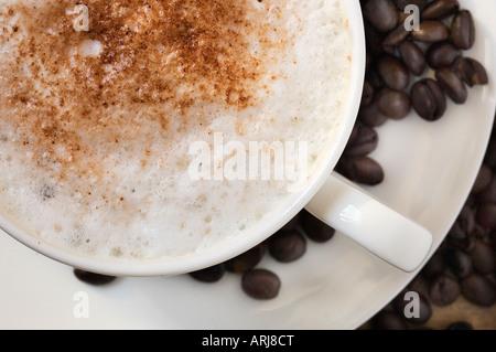Un gros plan de tasse de Cappuccino sur une soucoupe, entouré de grains de café torréfiés Banque D'Images