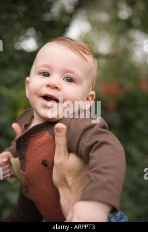 Près de six mois, bébé garçon qui aura lieu à l'extérieur par le père Banque D'Images