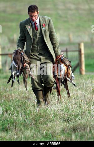 Garde-chasse avec sac du jour accolades de faisans anglais scène rurale Banque D'Images