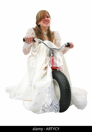 Une jeune mariée dans une robe de mariage, école un tricycle, faisant glisser le train derrière elle. Banque D'Images