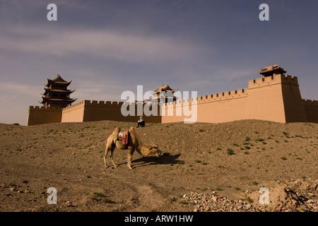 Jiayuguan Fort avec un chameau à l'extrémité ouest de la Grande Muraille de Chine. Banque D'Images
