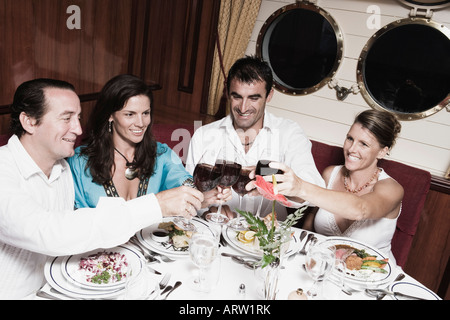 Deux Mid adult couples toasting with wine glasses and smiling Banque D'Images