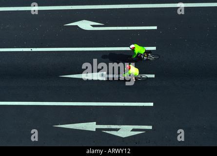 Vue aérienne de deux cyclistes équitation dans une rue avec des flèches peintes à Tokyo au Japon Banque D'Images