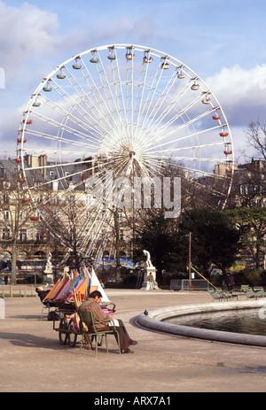 Paris Jardin des Tuileries étang avec l'homme assis à côté de location de bateaux à voile modèle fun et juste au Banque D'Images