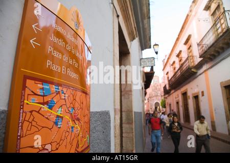 Mexique Guanajuato Directions flèches et la carte de sites touristiques en ville les gens marcher dans rue étroite Banque D'Images
