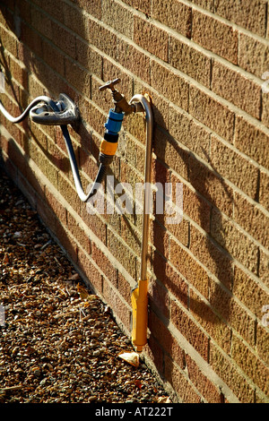 En dehors d'un robinet d'eau avec tuyau de jardin et arrière joint clapet restricteur de débit Banque D'Images