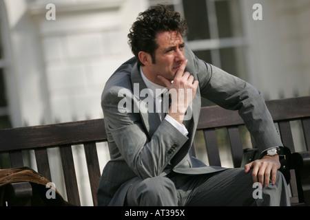 Un homme assis sur un banc de la pensée Banque D'Images