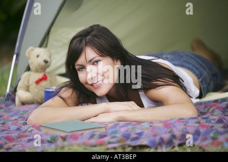 Un dark haired woman lying on a blanket devant une tente
