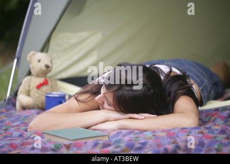 Une jeune fille aux cheveux noirs dormir sur une couverture devant une tente
