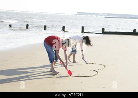 Un jeune couple dessiner une forme de cœur dans le sable Banque D'Images
