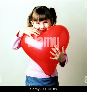 Une petite girl hugging a heart shaped balloon Banque D'Images