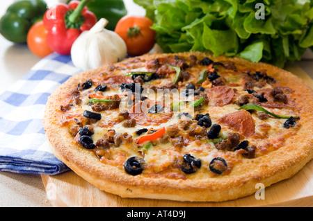 Une pizza chaude présentée avec des produits frais sur un plateau en bois Banque D'Images